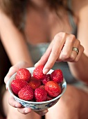 Woman taking a strawberry from bowl