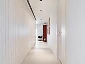 Schmaler Gang mit abgehängter Decke und weiss lackierter Holzverkleidung an Wand