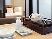 Tea service next to a rice wine carafe with porcelain bowls on an Asian style tray