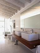 Weisses Designerbad mit lasierten Deckenbalken; wuchtige Aufsatzbecken auf massivem Holzwaschtisch