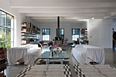 Abgedeckte Sofas an gläsernem Couchtisch im modernen Loft