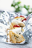 A grilled bread, feta and tomato kebab in tin foil