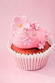 Cupcake mit pinkfarbener Creme und Zuckerblüten