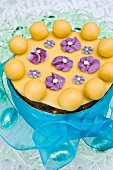 An Easter fruit cake decorated with marzipan balls and sugar violets