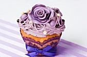A cupcake decorated with purple sugar roses