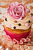 A cupcake decorated with a pink sugar rose and buttercream