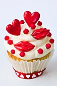 A cupcake decorated with red lips and hearts for Valentine's Day