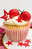 A cupcake decorated with marzipan strawberries and red stars