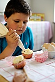 Young boy icing cupcakes