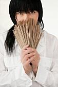 Asiatische Frau in weißem Hemd mit japanischen Sobanudeln vor dem Gesicht