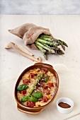 Gratinated green asparagus, fish, tomatoes, cheese, nutmeg and basil