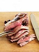 Roast lamb, sliced, on a choping board