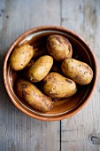 Fresh potatoes in a clay bowl
