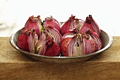 Roasted Red Onions with Garlic and Olive Oil in Tin Pan on Stone Surface