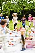 A garden party with children running about in the garden