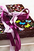 Chocolate cake decorated with sugar flowers, butterflies and a gift ribbon