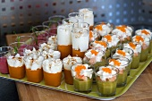 Various vegetable creams in glasses topped with whipped cream