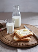 Buttered toast and milk on a wooden plate