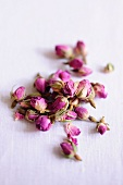 Dried rose buds on a white surface