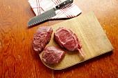 Raw Buffalo Sirloins on a Cutting Board with a Butcher Knife