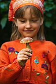 A girl holding a porcini mushroom