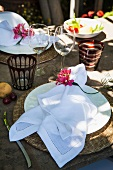 A white napkin with a flower decoration on a table laid in a rustic fashion