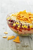 A layered salad with sweetcorn, beans and tortilla chips