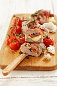 Stuffed pork fillet with mozzarella and tomatoes wrapped in bacon