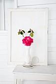 Rhododendron (Sorte: Abendsonne) in weisser Vase auf Tisch vor Holzpaneel
