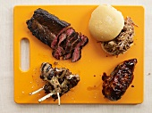 Assorted Barbecued Meat on an Orange Cutting Board