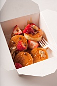 Mini Pancakes with Strawberries, Nuts and Honey in a Take Out Container