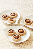 Sandies Cookies with Caramel and Chocolate on Small White Dishes