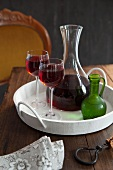 Red wine in a carafe and glass on a tray
