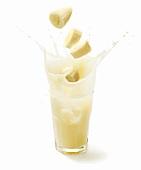 Bananenscheiben fallen in ein Glas mit Bananensaft