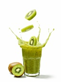 Kiwi slices falling into a glass of kiwi juice