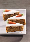 Three slices of carrot cake topped with icing and marzipan carrots