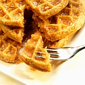 Stack of Five Grain Waffle with Organic Maple Syrup; Piece on a Fork