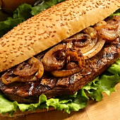 Grilled Steak and Onion Sandwich with Lettuce on a Roll