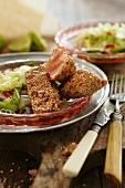 Salmon with a sesame seed crust on a bed of salad