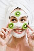 Frau mit Gesichtsmaske und Kiwischeiben