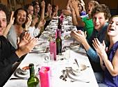 Menschen am Tisch klatschen in die Hände