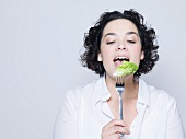 Frau hält Gabel mit Salatblatt