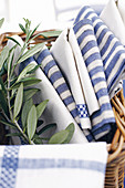 Various blue and white cloths and olive sprig in basket