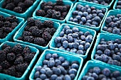 Baskets of Freshly Picked Blueberries and Blackberries at a Farmers Market