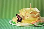 Rosenkuchen mit Schmetterlingsdeko und Kerze
