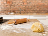 Mürbeteig mit Nudelholz auf bemehlter Arbeitsfläche in Küche