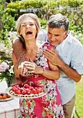 Älteres Paar im Garten; Mann versucht vom Kuchen zu naschen