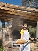 Frau vor Holzofen mit frisch gebackenem Brot auf Holzschaufel