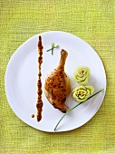 Duck Drumstick with Celery Flowers on a White Plate; From Above