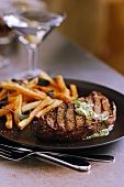 Grilled Steak with Herbed Butter and French Fries